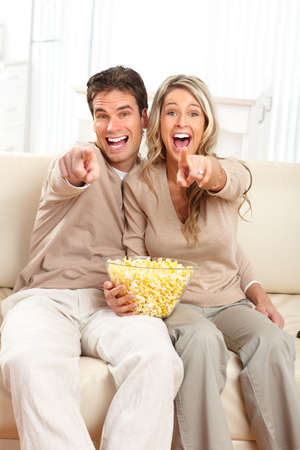 Young happy couple watching TV at home  photo