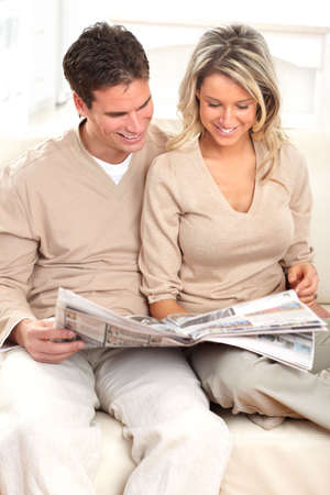 Young love couple reading a magazine  at home photo