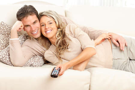 family sofa: Young happy couple watching TV at home  Stock Photo
