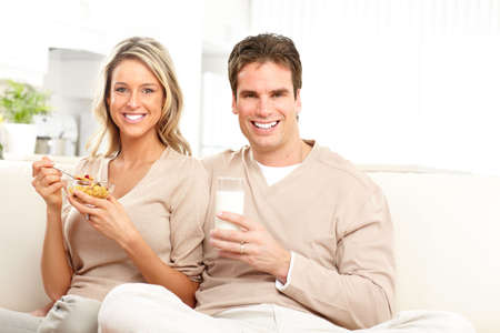 Young smiling couple having lunch at home  photo