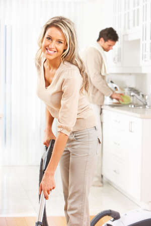 vacuum cleaning: Housework, vacuum cleaner, young couple, home, kitchen  Stock Photo