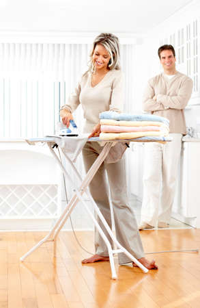 Happy young beautiful woman ironing clothes   photo