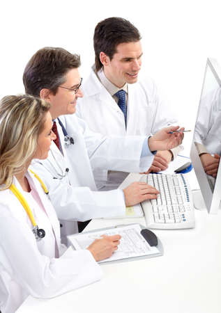 Smiling medical doctors with stethoscopes and computer. Isolated over white background  photo