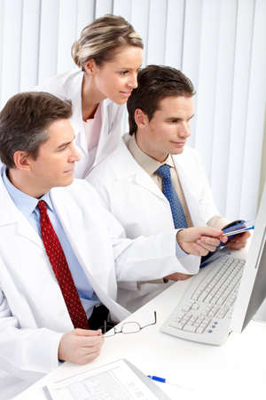 Smiling medical doctors with stethoscopes working with computer.  photo