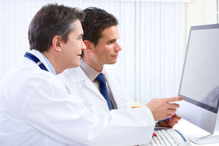 Smiling medical doctors with stethoscopes and computer. Stock Photo - 6459133