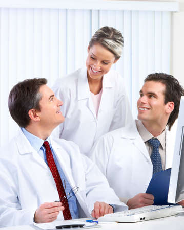 Smiling medical doctors with stethoscopes and computer.   photo