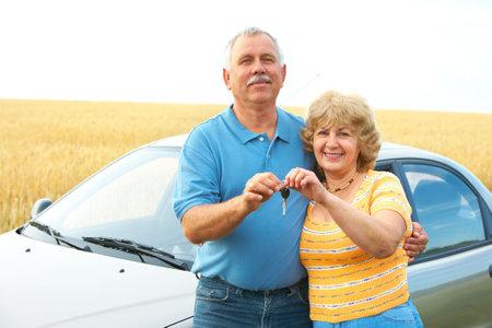 Smiling happy elderly seniors couple near the new car  photo
