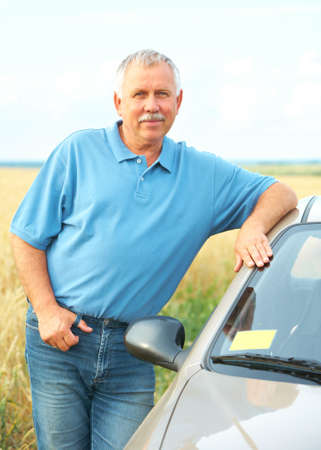 Smiling happy elderly senior  man  near the new car