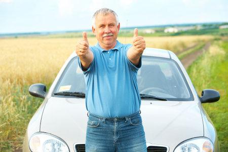 pollution free: Smiling happy elderly senior  man  near the new car