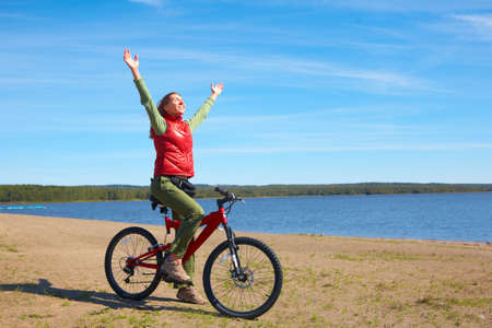 road bike: Young smiling  woman cycling near the lake   Stock Photo