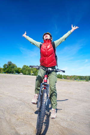 Young smiling  woman cycling in the park  Stock Photo - 6509771