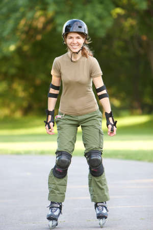 roller: Young smiling woman in park. Roller skates