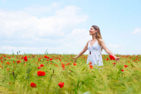 field of flowers: Happy young woman in the field under blue sky