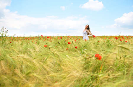 Happy young woman in the field under blue sky  photo