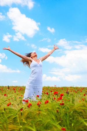 Gelukkig jonge vrouw onder de blauwe hemel  Stockfoto
