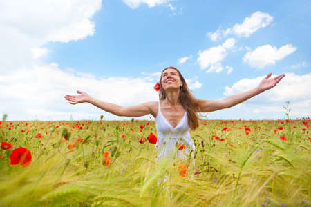 carefree: Happy young woman in the field under blue sky