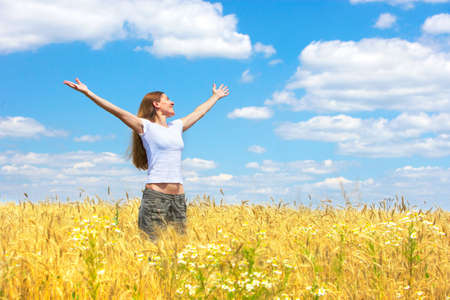 harvest field: Happy young woman in the field under blue sky