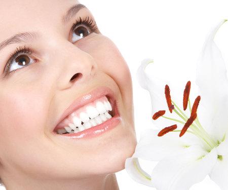 Mooie jonge vrouw die lacht met bloem. Geïsoleerd op witte achtergrond