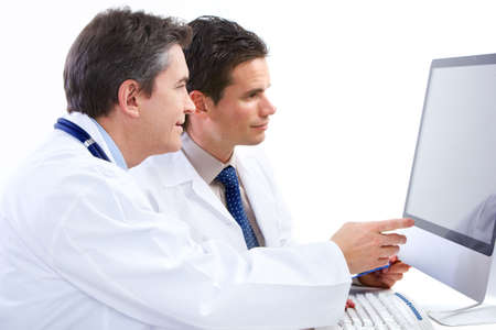 computer lab: Smiling medical doctors with stethoscopes and computer. Isolated over white background  Stock Photo