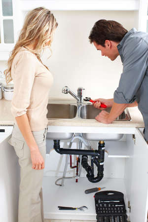 Young plumber fixing a sink   photo
