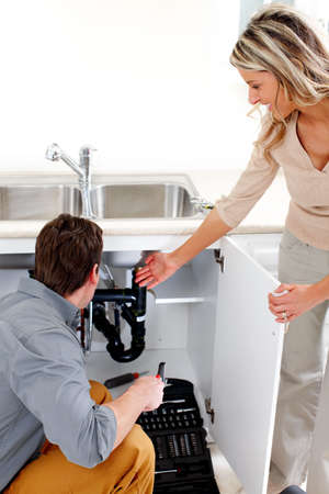 Young plumber fixing a sink   Stock Photo