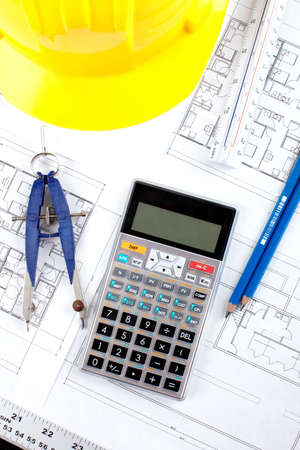 pencil and calculator over a construction drawing of a house