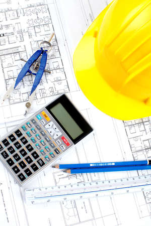 budget repair: pencil and calculator over a construction drawing of a house