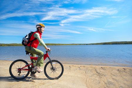 Jonge lachende vrouw fietsen in de buurt van het meer  Stockfoto