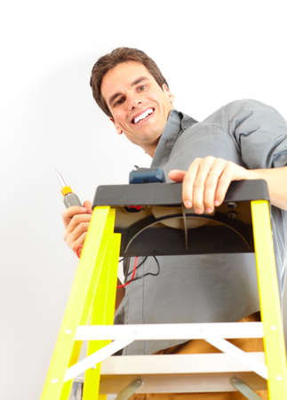 energy work: Young smiling electrician doing his work
