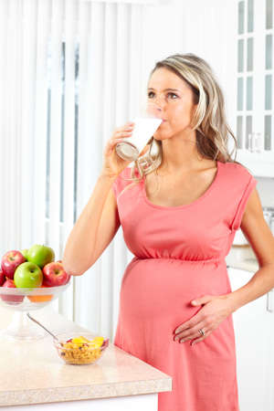 pregnant woman drinking milk at kitchen