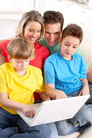 Happy family. Father, mother and boy working with laptop.   photo