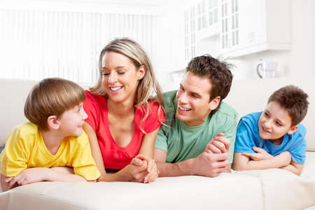 woman on couch: Happy family. Father, mother and children at home
