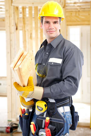 constructors: Young handsome builder with wood planks