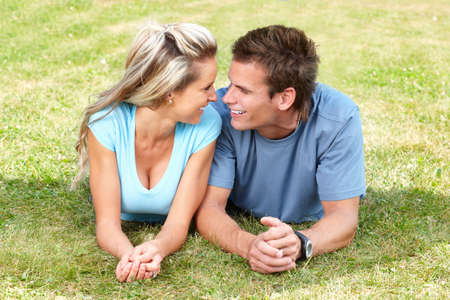Young smiling  love couple on green grass