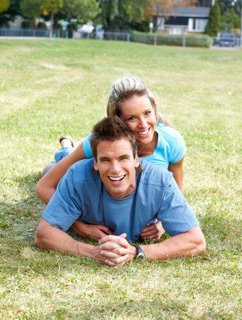 Jóvenes sonriendo amor pareja sobre césped verde