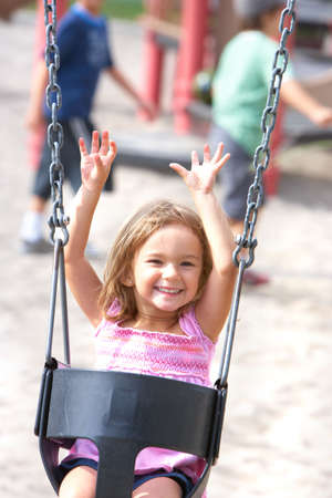 Happy  little girl swinging in the park  photo