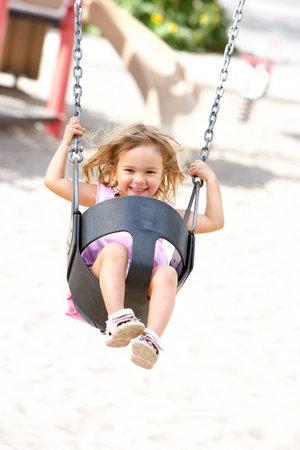 columpio: Ni�a feliz, oscilando en el Parque  Foto de archivo
