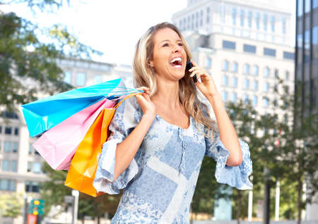 Happy shopping  woman calling by cellular outdoor  photo