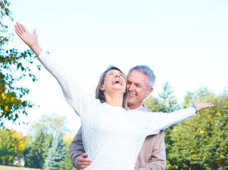 retire: happy  elderly seniors couple in the forest