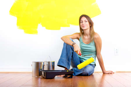 wall decor: Smiling beautiful woman painting interior wall of home.  Renovation  Stock Photo