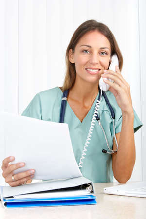 Smiling medical doctor with telephone. Over white background Stock Photo - 6744381