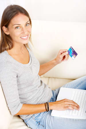 Beautiful smiling woman with laptop  and a credit card  photo