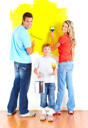 children painting: Renovation. Young family painting interior wall of home.   Stock Photo