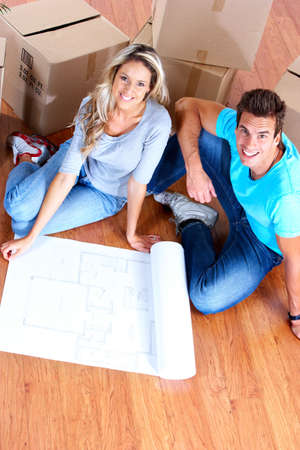 young couple sitting on the floor and looking at blueprints. Archivio Fotografico