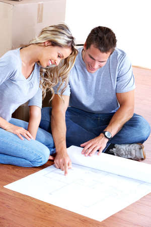 young couple sitting on the floor and looking at blueprints.