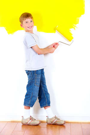 smiling boy painting interior wall of home.   Stock Photo