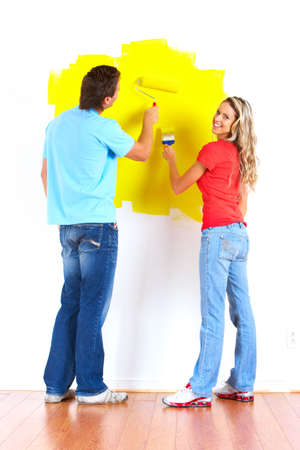 smiling couple painting interior wall of home.   版權商用圖片