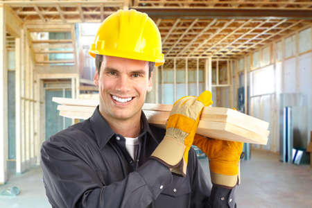 Young handsome builder with wood planks