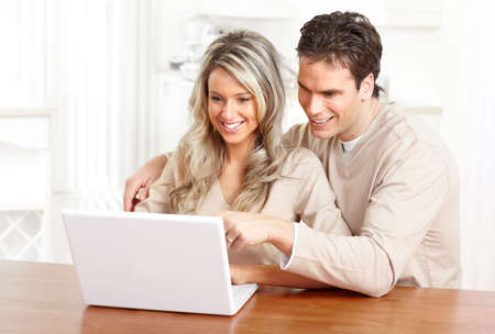 laptop: Young happy couple in love with laptop at home  Stock Photo