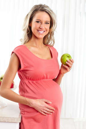 Smiling beautiful pregnant woman with an apple  photo